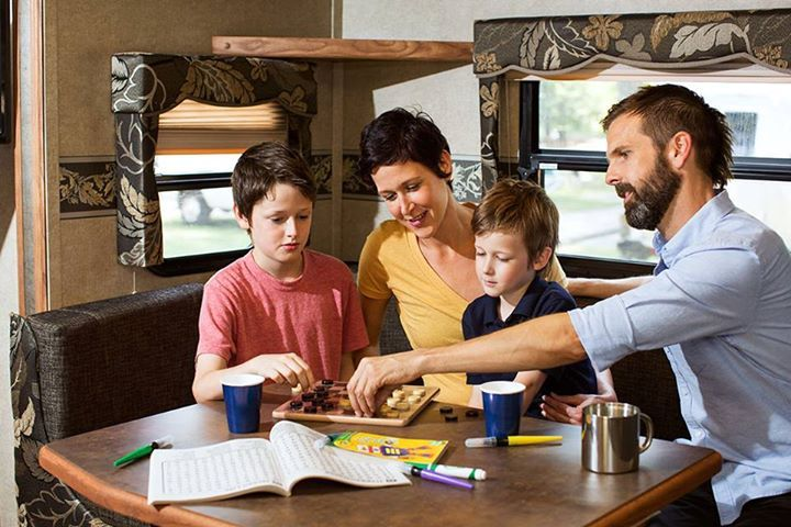 Family playing games in their traveling camper RV