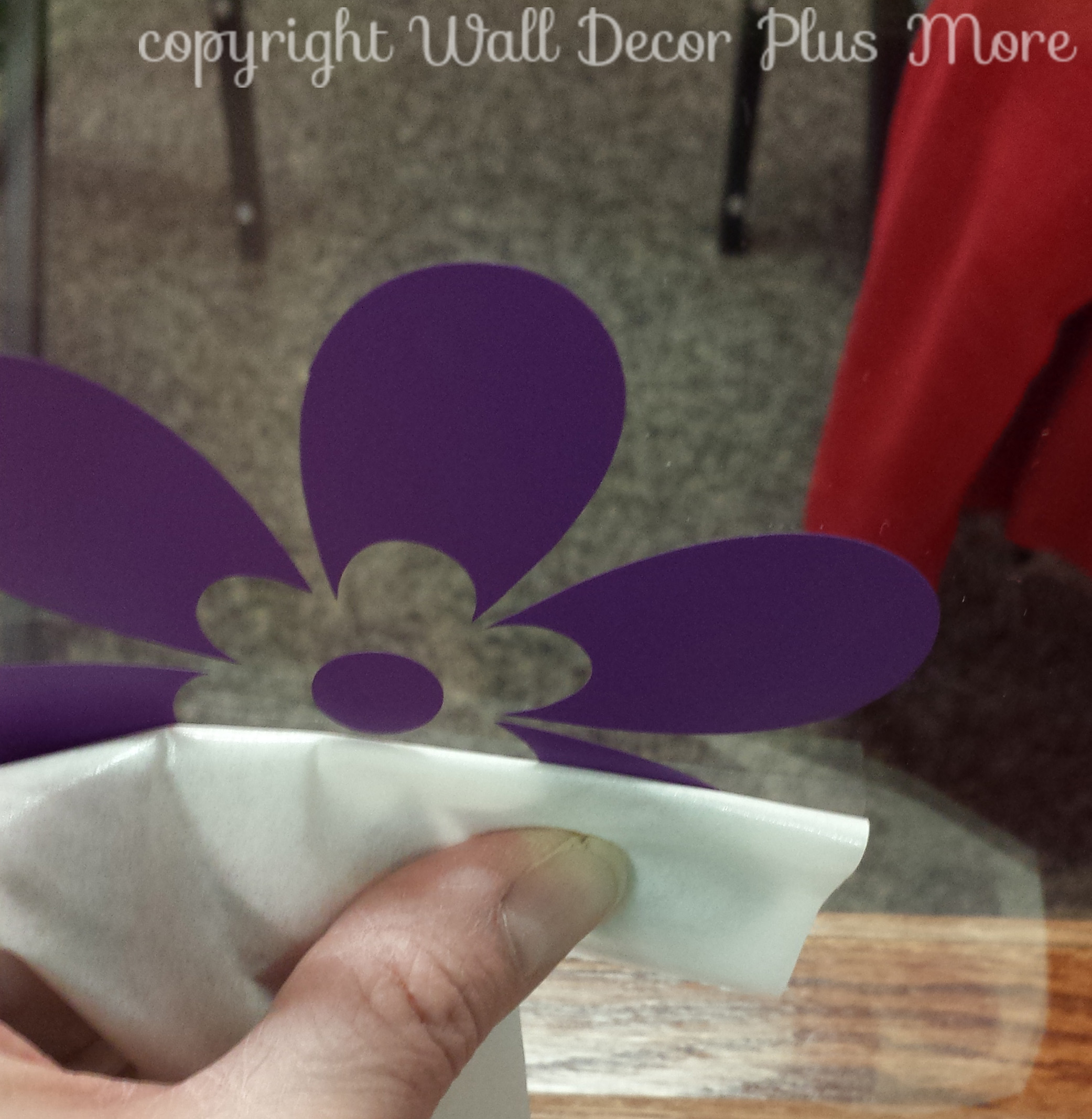 Peeling the top transfer paper off floral wall decals